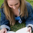 Young relaxed girl lying on the grass while reading a book — Stock Photo #10328819
