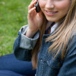 Stock Photo: Young smiling girl talking on phone while sitting down in a