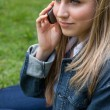 Stock Photo: Young blonde womcalling with her mobile phone while sitting i