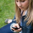 Stock Photo: Young girl sending text while sitting on grass
