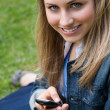 Stock Photo: Young blonde girl sitting on grass while sending text