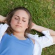 Stock Photo: Young relaxed girl napping on grass while placing her hands