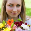 Young relaxed girl holding a bunch of flowers in a public garden — Stock Photo