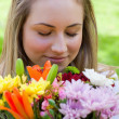 Young blonde girl closing her eyes while smelling a bunch of flo — Stock Photo #10328880