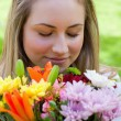 Young blonde girl closing her eyes while smelling a bunch of flo — Stock Photo