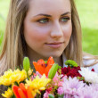 Young relaxed blonde girl holding a bunch of flowers while looki — Stock Photo #10328884