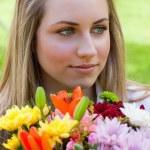 joven rubia relajada sosteniendo un ramo de flores mientras looki — Foto de Stock   #10328884
