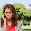 Woman looking towards the ground while on the phone in a bright — Stock Photo #10328914