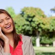 Young woman laughing happily on the phone in a bright park area — Stock Photo