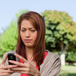 Serious woman reading a text message in a bright grassland area — Stock Photo