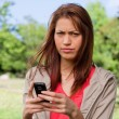 Woman with a stern expression on her face while holding a phone — Stock Photo