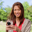Stock Photo: Young womsmiling happily while holding phone