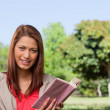 Woman smiling while looking straight ahead with a book in her ha — Stock Photo #10328946