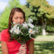 Woman smelling a bunch of flowers while standing in a park — Stock Photo
