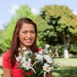 Woman looking into the distance and holding a bunch of flowers — Stock Photo