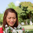 Young woman examining a bunch of flowers while standing in a par — Stock Photo