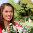 Woman looking towards the side flowers in a park — Stock Photo #10328979