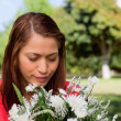 Young woman looking down at a flowers while standing in a park — Stock Photo #10328981