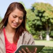 Young woman using a tablet while standing in bright park — Stock Photo #10328982