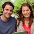 Man and a woman look ahead while holding a tablet — Stock Photo