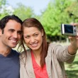 Woman takes a picture of her friend and herself with a camera — Stock Photo