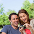 Stock Photo: Two friends smiling happily as look at photo collection