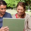 Man holds a tablet as he and his friend watch something on its s — Stock Photo #10329014