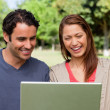 Two friends laughing as they watch something on a tablet — Stock Photo