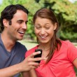 Man laughing as he shows something on his phone to his friend — Stock Photo #10329036