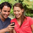 Two friends smiling as they are looking at something on a mobile — ストック写真