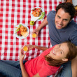 Stock Photo: Elevated view of two smiling friends as they lie on blanket wi