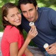 Stock Photo: Two smiling friends looking upwards while holding ice cream