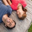 Two friends looking towards the sky while lying on a quilt — Stock Photo