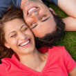 Two friends smiling while lying head to shoulder with an arm beh — Stock Photo #10329144