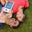 Two friends using a camera while lying side by side — Stock Photo #10329179