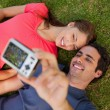 Man taking a photo with his friend while lying side by side — Stock Photo #10329181