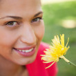 Woman smiling as she looks upwards while holding a yellow flower - Stock Photo