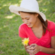 Woman laughing while wearing a white hat and holding a yellow fl — Stock Photo
