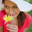 Woman wearing a white hat while smelling a flower while looking — Stock Photo