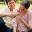 Woman smelling a flower which is being given to her by a man — Stock Photo #10329374