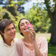 Man watching his friend while she is smelling a flower — Stock Photo