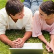 Stock Photo: Two friends looking at each other as they lie down with a laptop