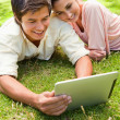 Woman leans against her friend as they use a tablet together — Stock Photo