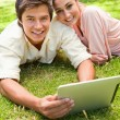 Two friends looking ahead as they use a tablet together — Stock Photo #10329425