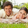 Two friends smiling and looking ahead while lying on a blanket - Stock Photo