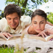Two friends looking down at books while lying on a blanket — Stock Photo
