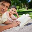 Two friends looking to the side while reading in a park - Stock Photo