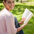 Woman looks to her side while reading a book in a park — Stock Photo