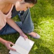 Woman looks down at a book while sitting on grass - Foto Stock