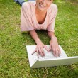 Stock Photo: Woman looking ahead while using a laptop as she lies down in gra